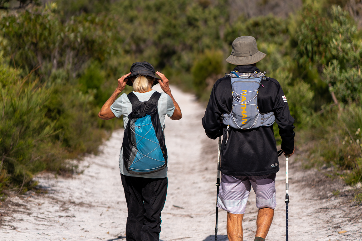 Man and woman hiker in loose clothing wearing hats and water bladder packs.