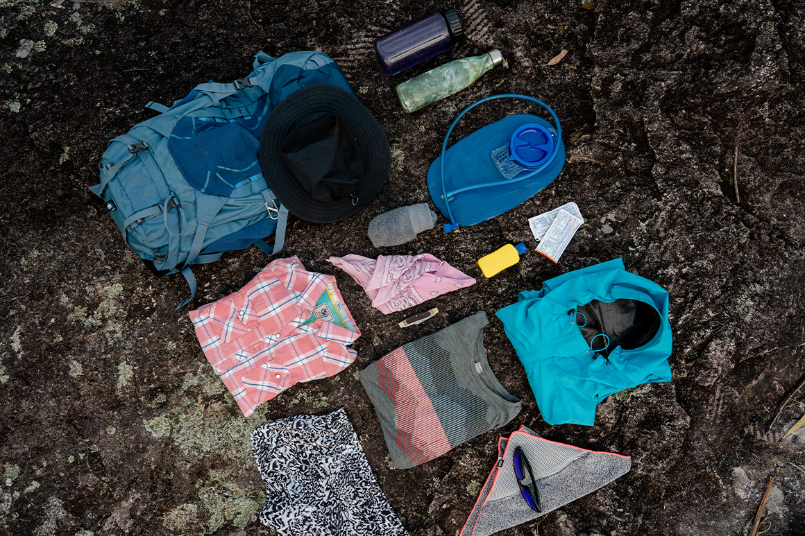 Hiking equipment including a water bladder, water bottle and spare clothes laid out on a rock.