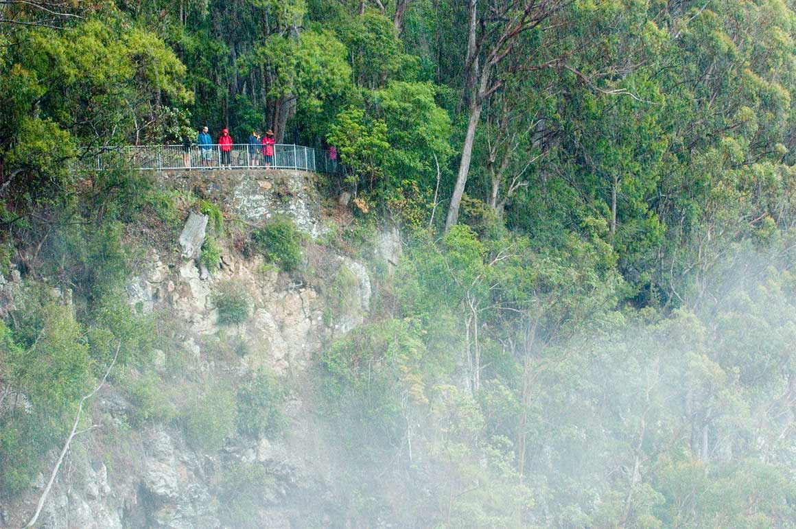 Mist rises from a waterfall to meet people standing at a lookout surrounded by rainforest high above a sheer cliff face.