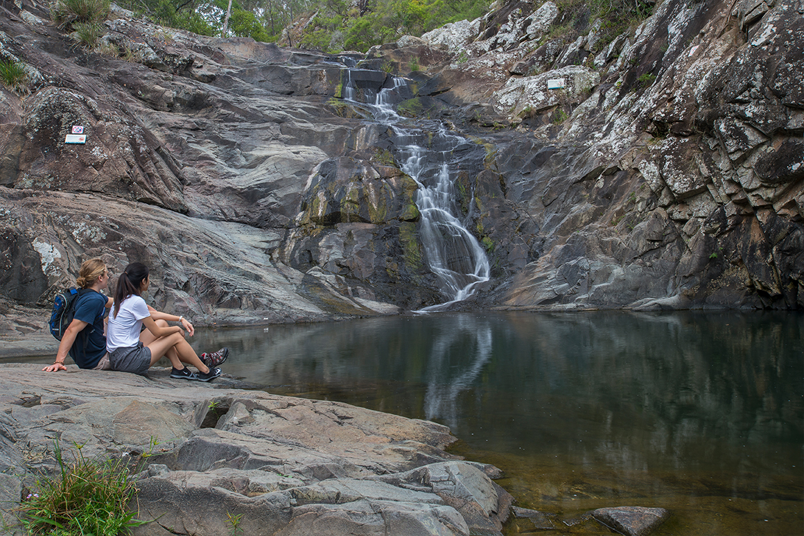 Two people sit on a rock with a rockpool and waterfall in the background.
