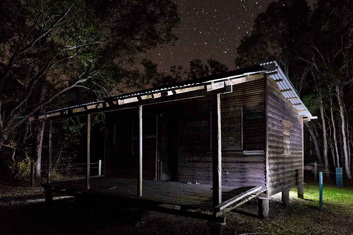 Historic wooden hut is dimly lit under a starry night sky surrounded by tall ghostly trees.