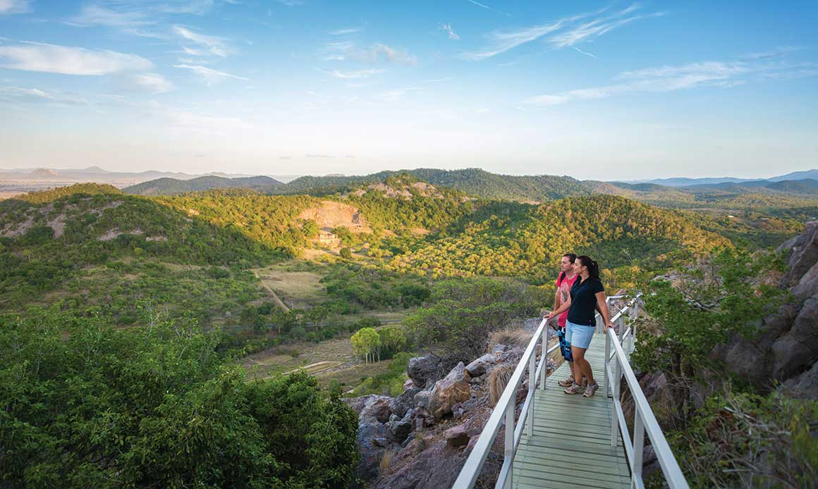 Couple stand on elevated walkway winding around a limestone outcrop, overlooking rolling limestone hills clad in dry rainforest.