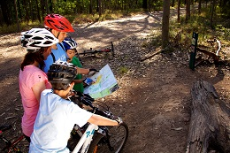 Family of mountain-bike riders stopped on the side of a trail reading a map.