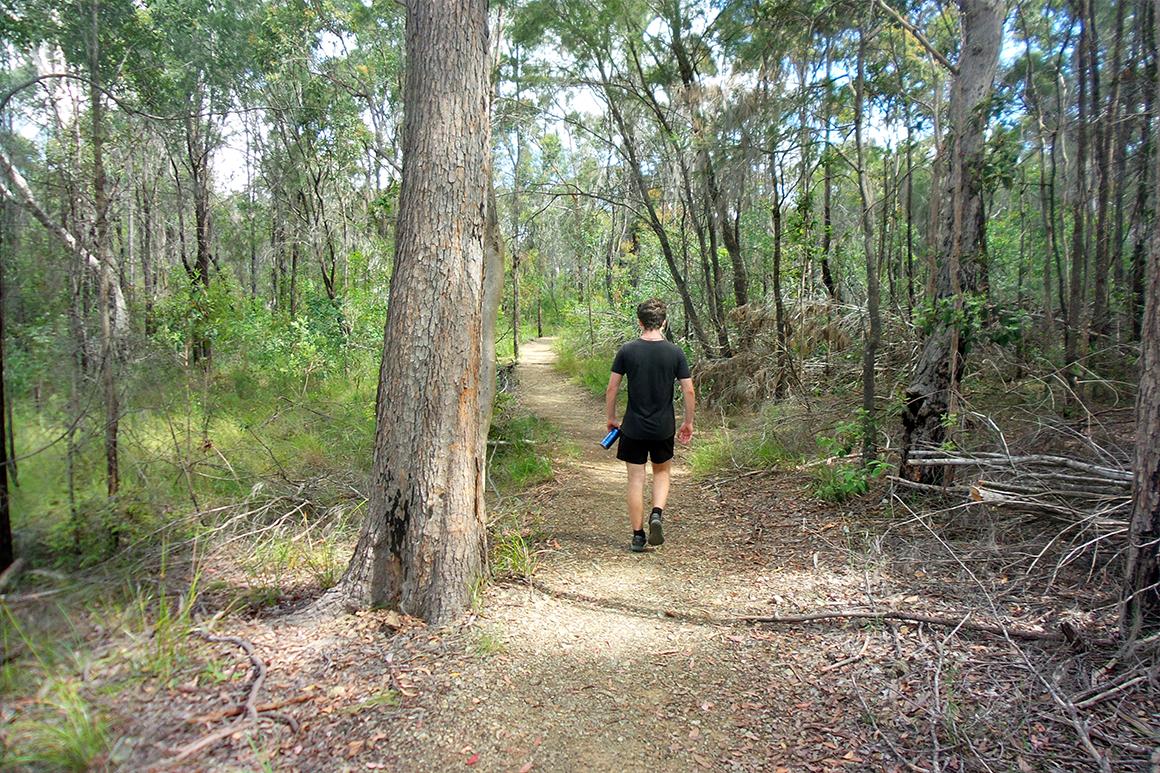 Teenager powerwalks along a level track through open woodland.