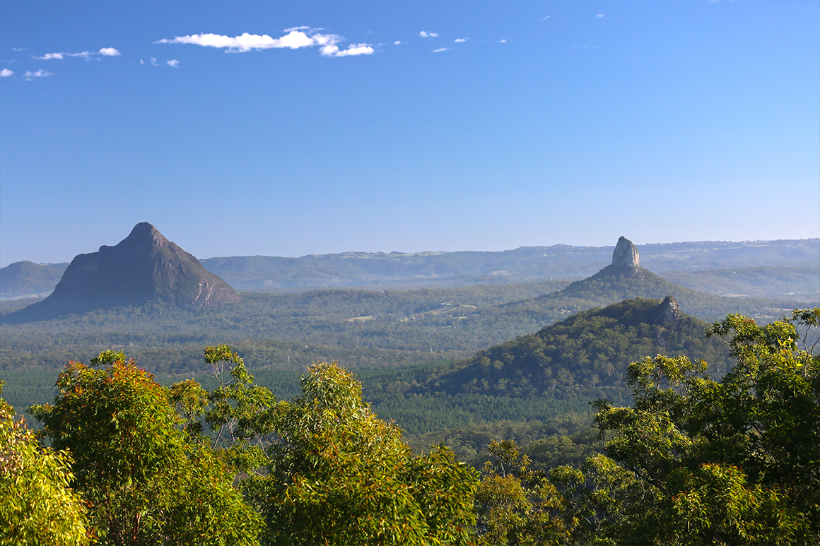 View from high vantage point of Glass House Mountain peaks rising from coastal plain.