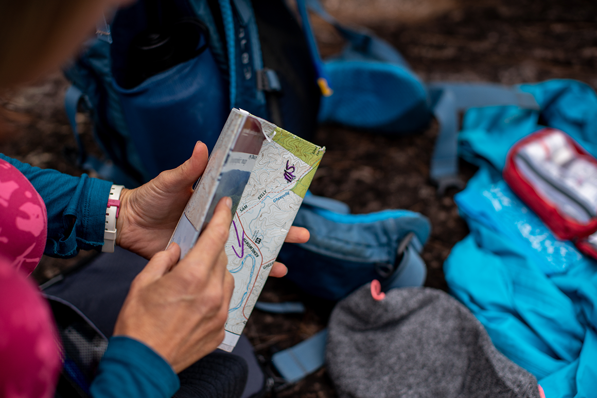 Hiker inspecting a park map with scattered gear in the background.