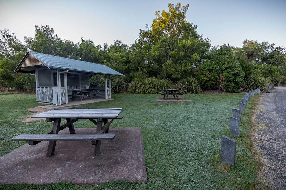 Undercover barbecue area and two picnic tables in an open, grassy area in The Settlement camping area.