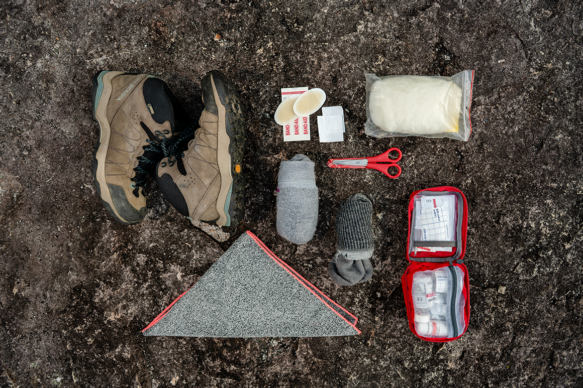 Hiking boots, socks, a towel and the contents of a first aid kit are laid out on a rock.