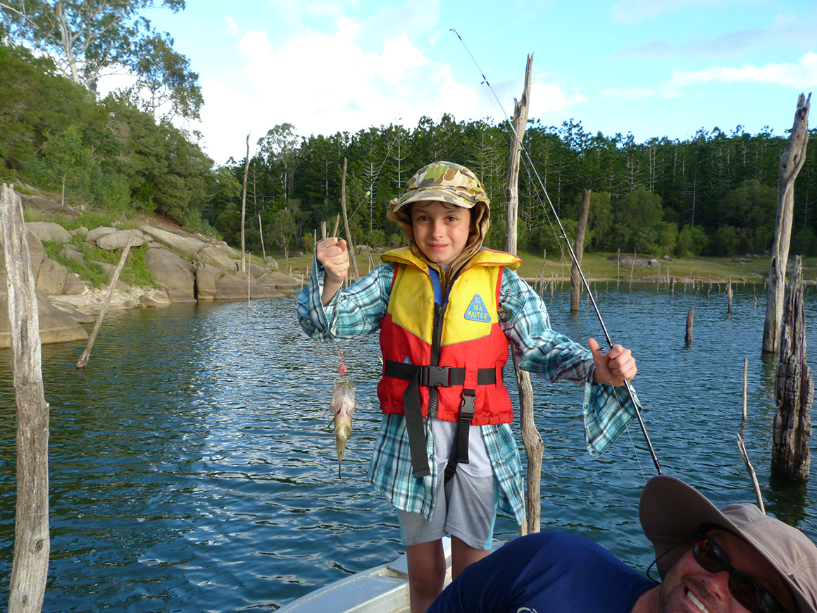 Young boy in camoflaged hat and wearing red and yellow like jacket holds fishing rod in one hand and small fish in th eother hand while standing proudly in the tinnie on the blue water of the lake.