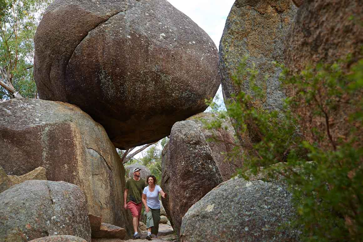 A couple walking under massive granite boulders balanced on each other to form an archway.