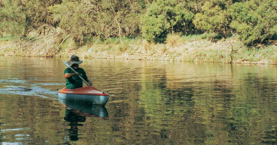 A man in green t-shirt and hat paddling an orange canoe on wide section of river with bushy riverbank in the background.