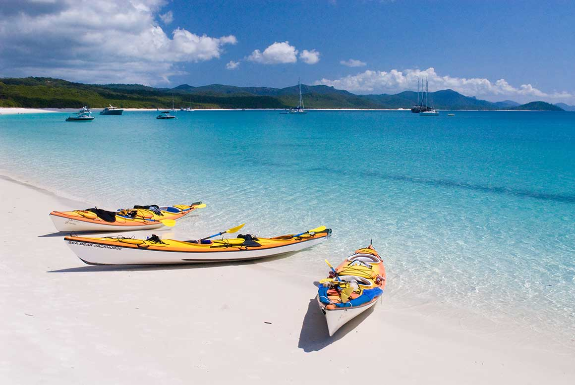 Three yellow kayaks lie on a white sandy beach with the bright blue ocean as a backdrop.