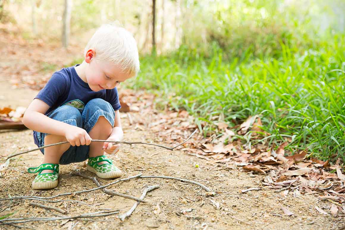 Young fair-haired boy crouches on track with stick in hand, other sticks at his feet (encased in cute green spotted shoes), fully absorbed in what he is doing.