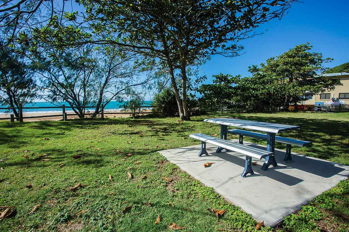 Picnic table sits on concrete pad surrounded by neatly mown green grass with a few trees along the shore and blue ocean in the background