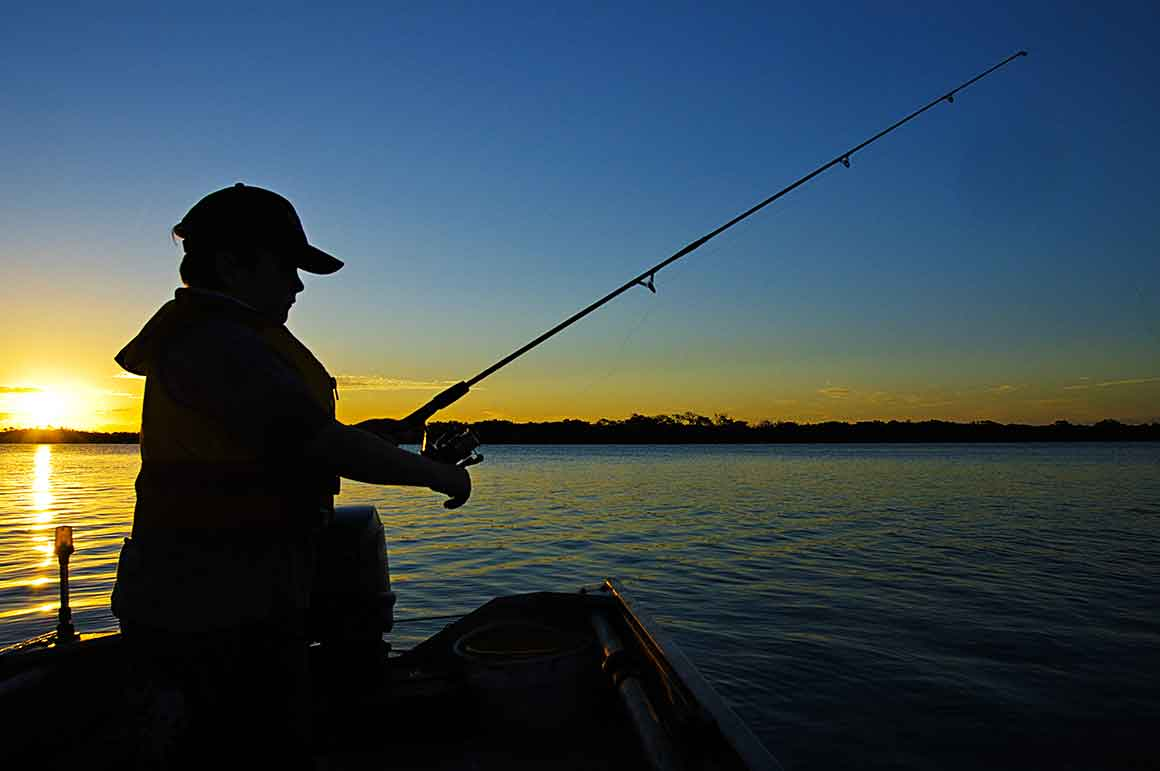 Black silhouette of a person with cap and rod fishing from a jetty against a bright blue sky with a line of golden sunset along the horizon