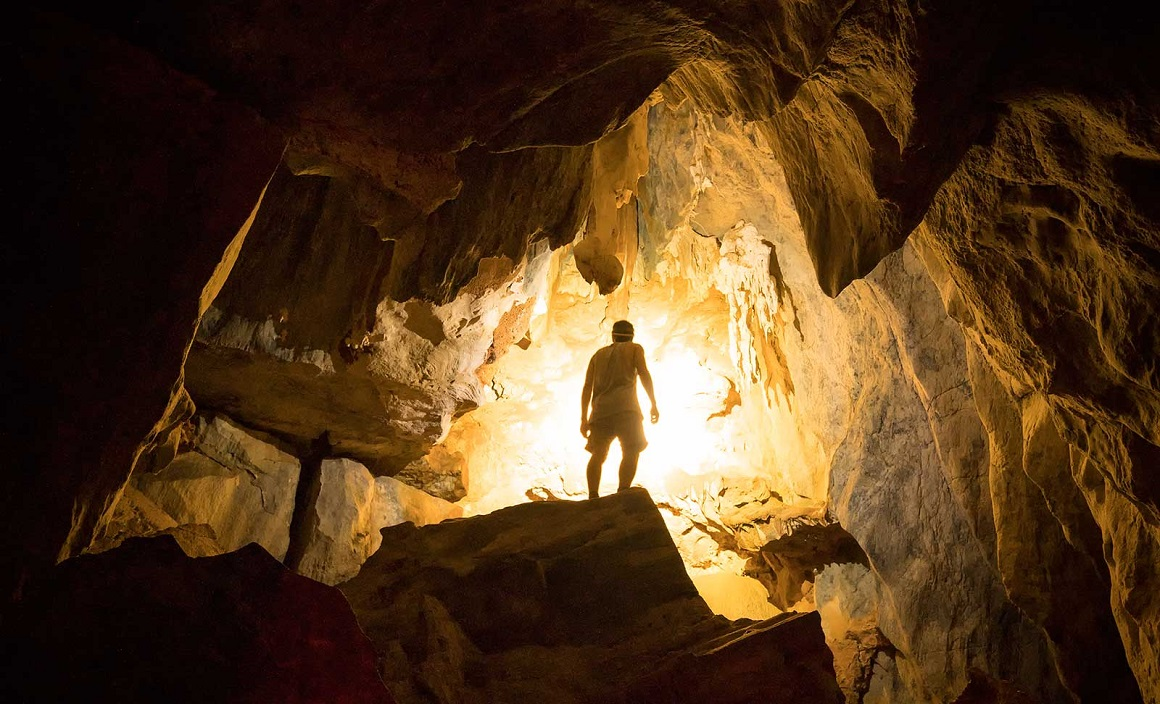 Man stands on top of rock inside cave, silhouetted against the golden light pouring in from the small cave entrance, lighting up the surrounding darkness
