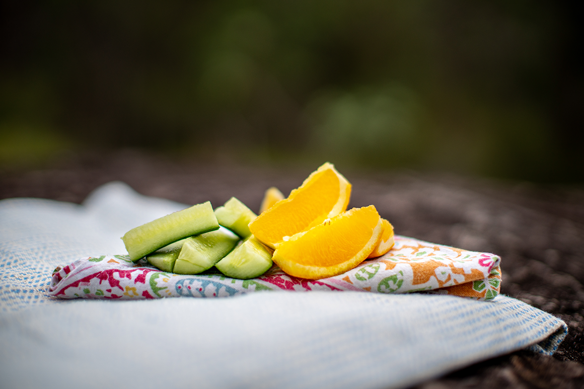 Pieces of cut orange and apple on a wax wrap laid out on a rock.
