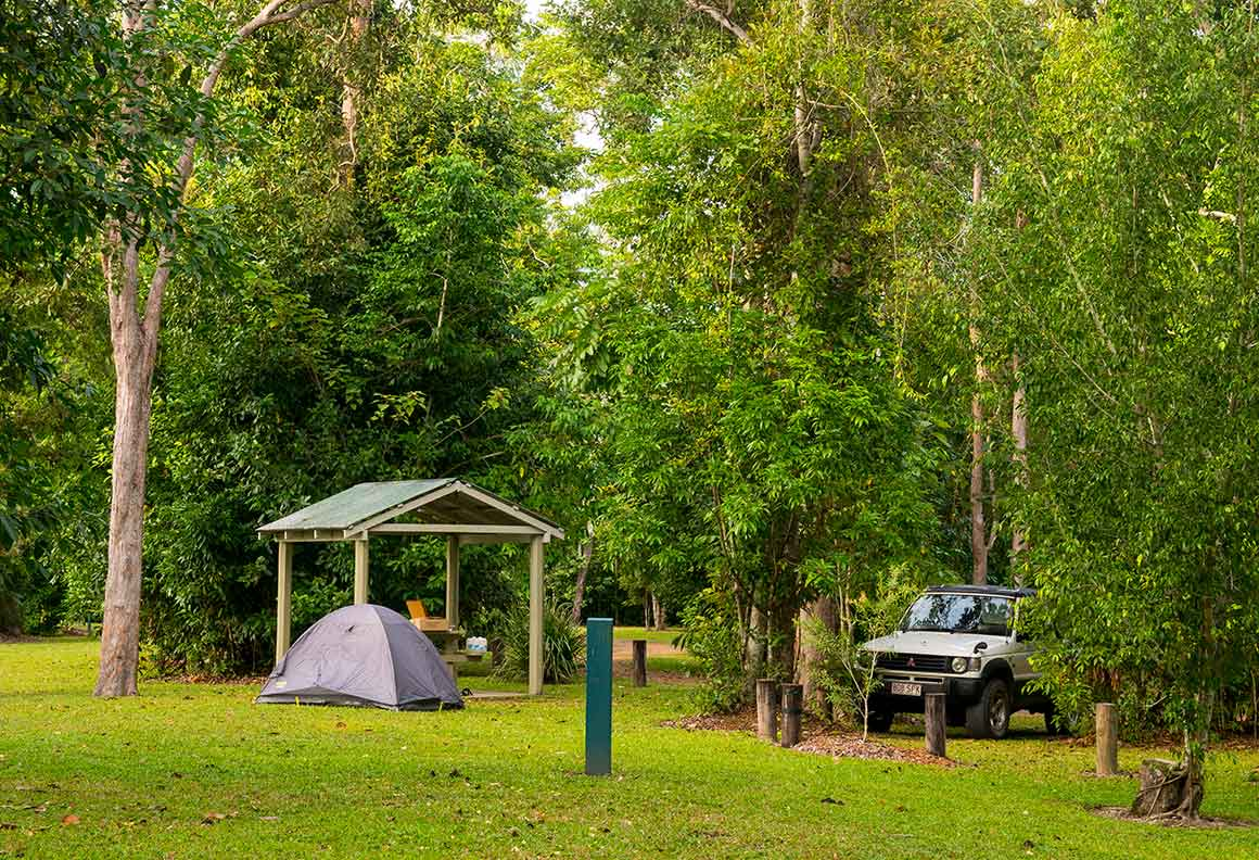 Small domed tent pitched in grassy clearing beside picnic shelter and parked vehicle, surrounded by tall trees.