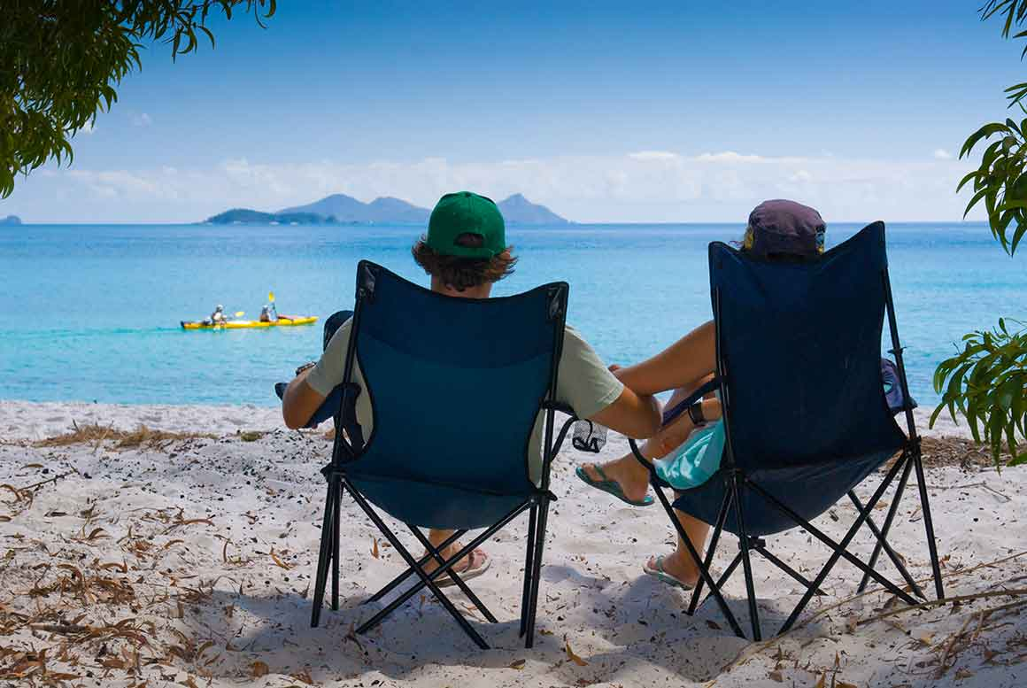 A couple relaxes in camp chairs, facing the bright blue waters of the ocean, where people paddle a yellow kayak across the blue ocean and a high island seemingly floats near the horizon.