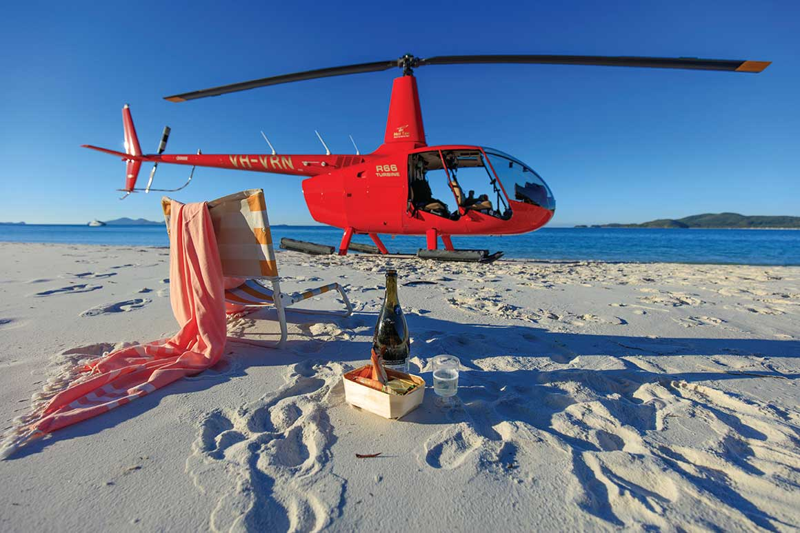 Red helicopter on sandy beach in background with picnic lunch and chair in the foreground.
