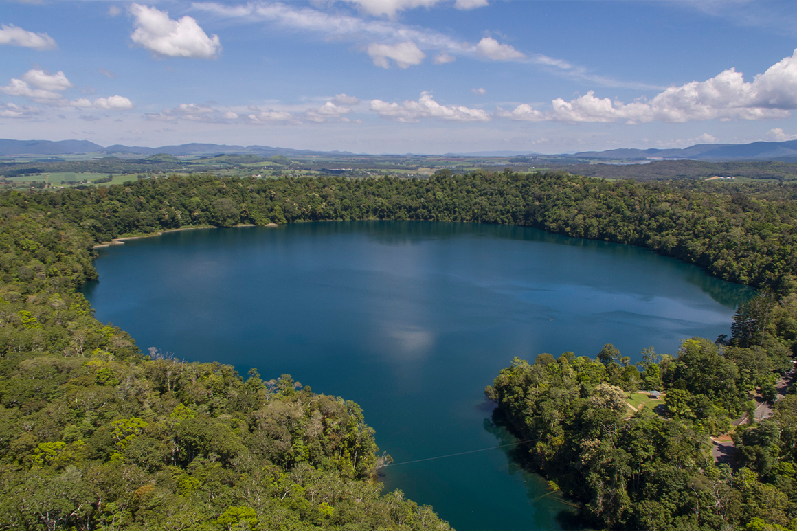 Alt text< aerial view over round blue lake surrounded by dense green rainforest with mountains in the distance.