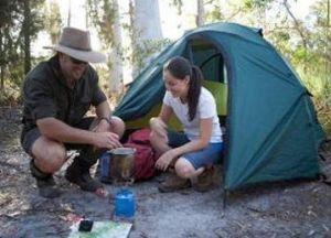 Photo of two people crouched in front of a tent.