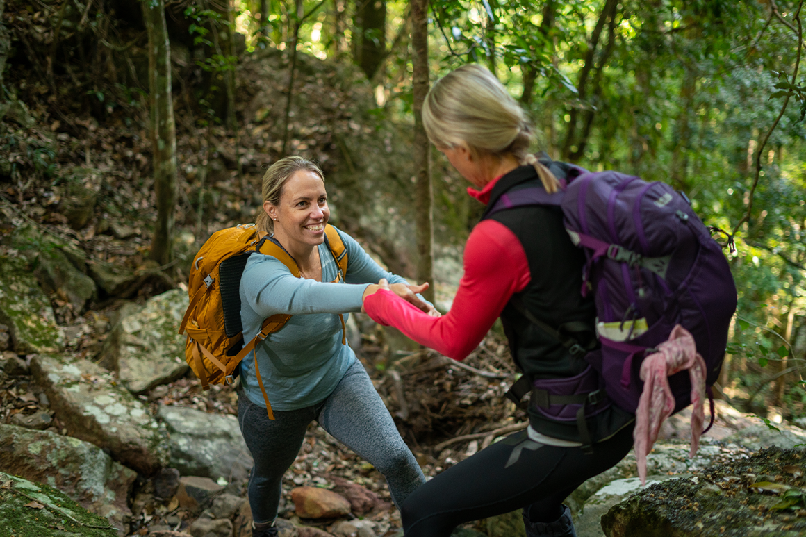A hiker helps another hiker over uneven ground.