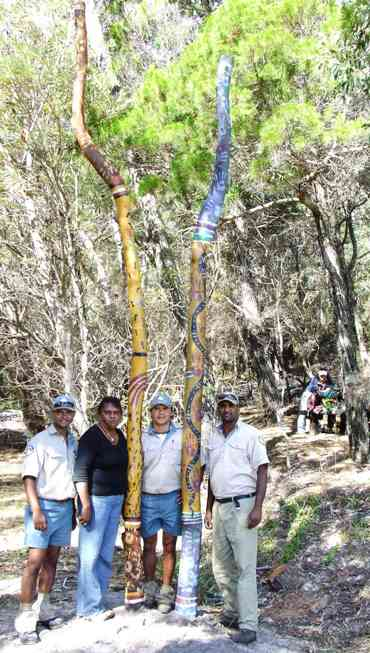 Welcome poles located near McKenzie's jetty, K'gari. L-R: Conway Burns; Jan Williams; Bevan Page; Jarred Appo. Photo: Peter Wright, Queensland Government