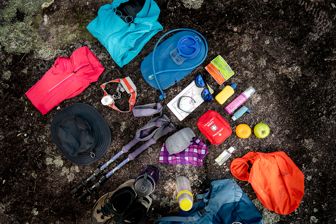 A selection of hiking equipment, including wet weather clothes, first-aid-kit, water bottle and headlight, is laid out neatly on a rock.