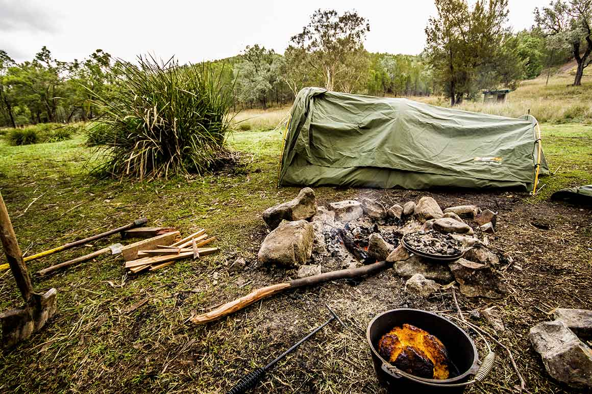 Swag tent set up on grass in camp site beside a smouldering camp fire, with camp gear lying around, and forested hill in background.