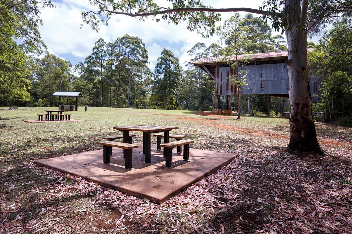 Picnic tables and picnic shelters are set in an open grassy space with an historic corrugated iron building and surrounding forest in the background.