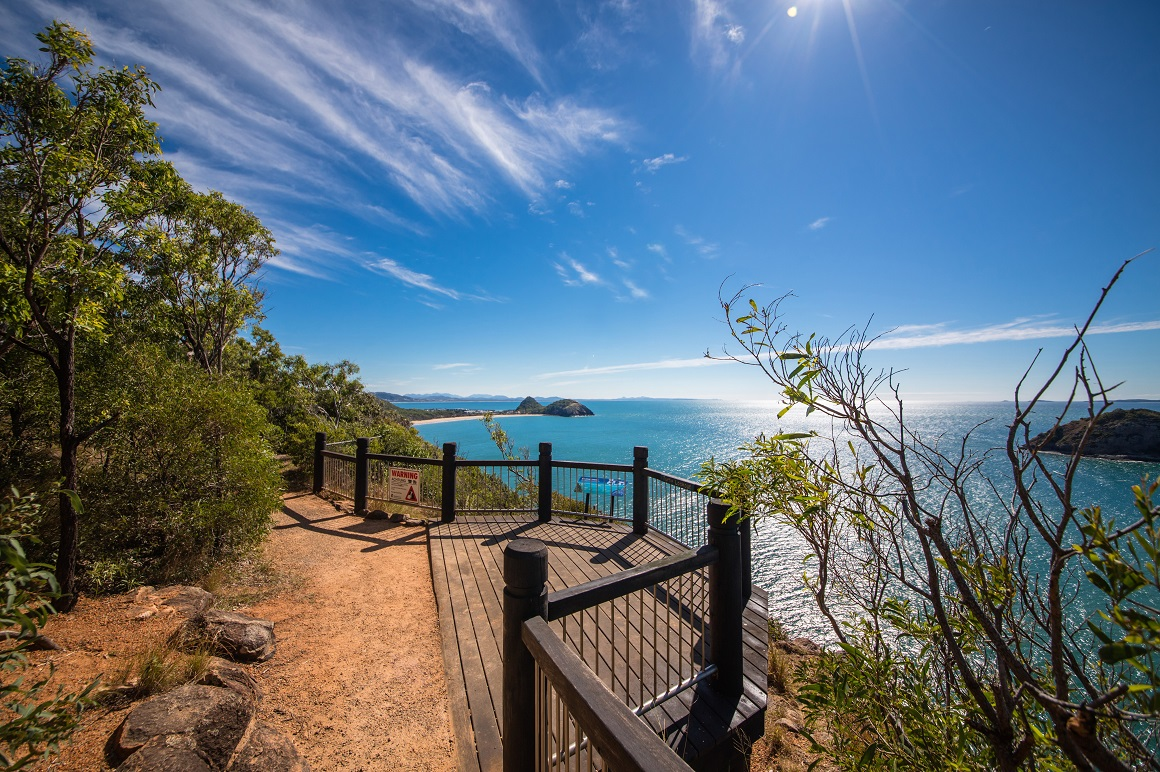 Clear blue skies are reflected in shimmering blue ocean from a coastal lookout atop a bluff with mountainous coastline in the distance.