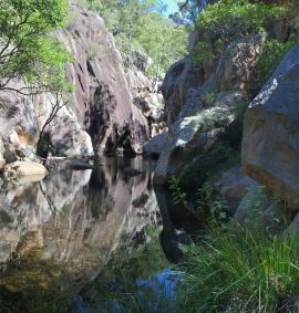 The 3.7km walk to the Lower Portals is rewarded with an opportunity to dip a toe into a deep pool set within a rocky gorge. Always read the warning signs and supervise children at all times. Photo: Alison Ilic, Queensland Government.
