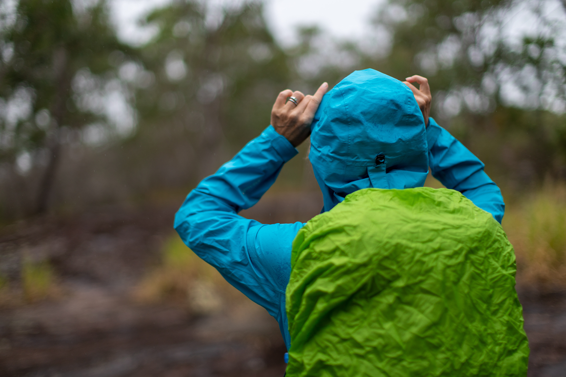 Hiker wears a rain jacket and has cover on her day pack.