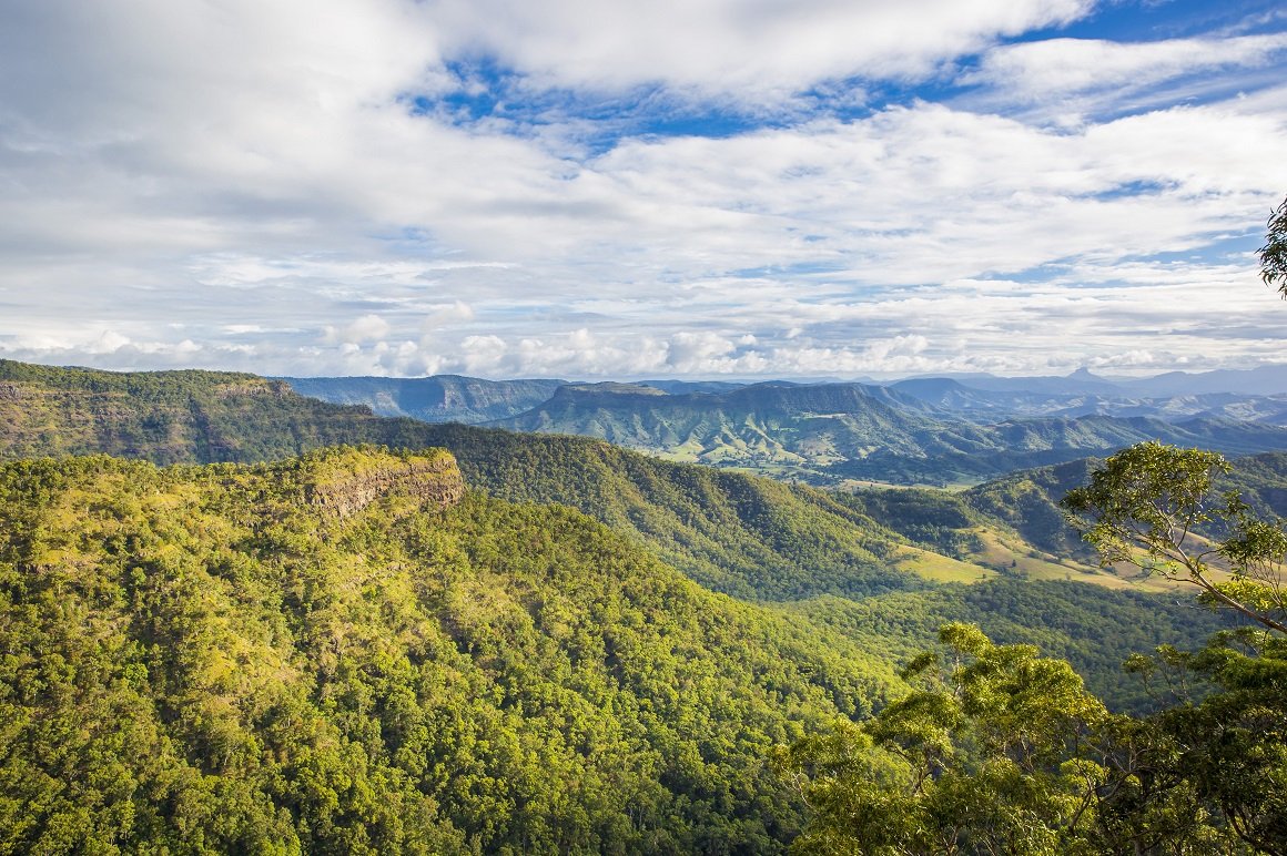 Vast blue cloudy skies sit above lines of green-clad ranges stretching into the hazy blue distance.