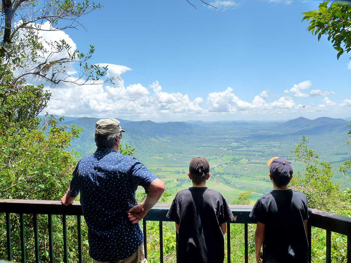 A grandfather and two young boys gaze over a green valley and distance mountains from a lookout