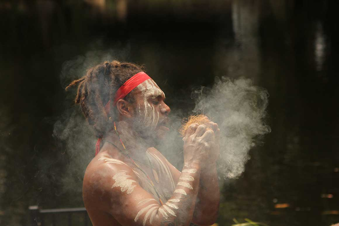 : Aboriginal performer in red head band and dreadlocks, painted up with white ochre, creates fire as smoke rises around him.
