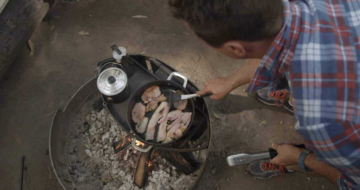 Man cooking up bacon on a small barbecue in D'Aguilar National Park