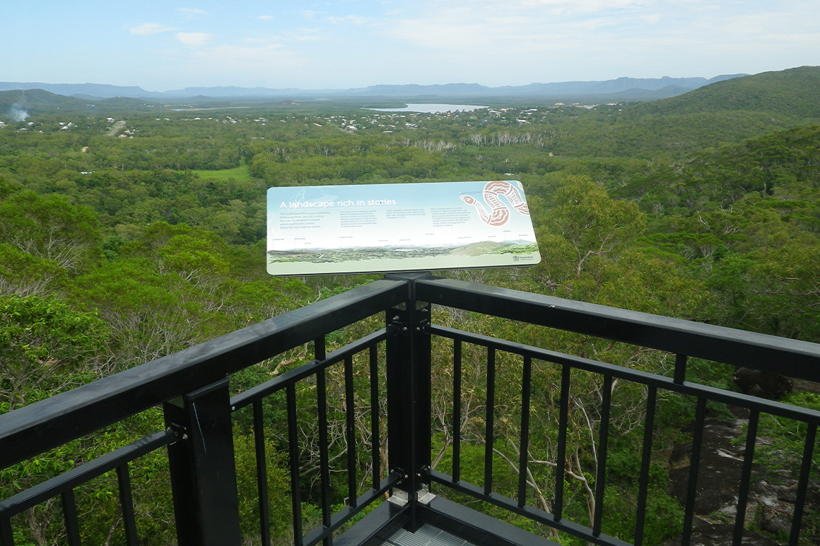 Platform rails and interpretive sign in foreground with view over woodlands and coastline in background.