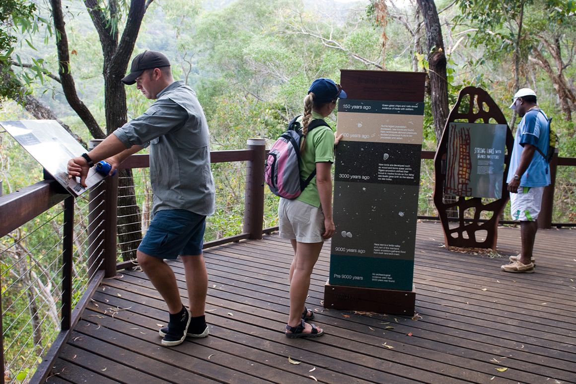 Visitors interacting with interpretive signage on a wooden lookout platform at the Nara Inlet cultural site.