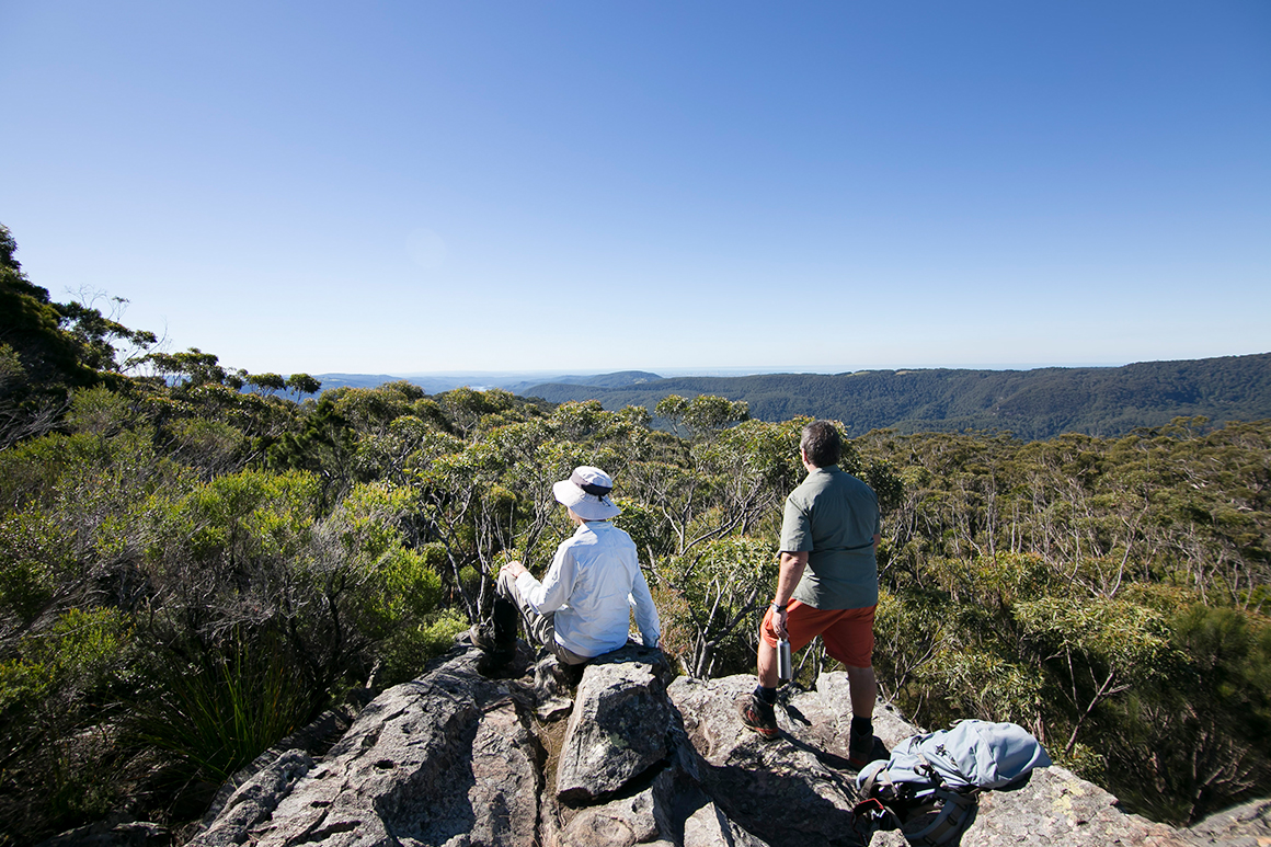 Two bushwalkers sit and stand atop a rocky outcrop looking over forest canopy and towards a distant blue ridgeline.