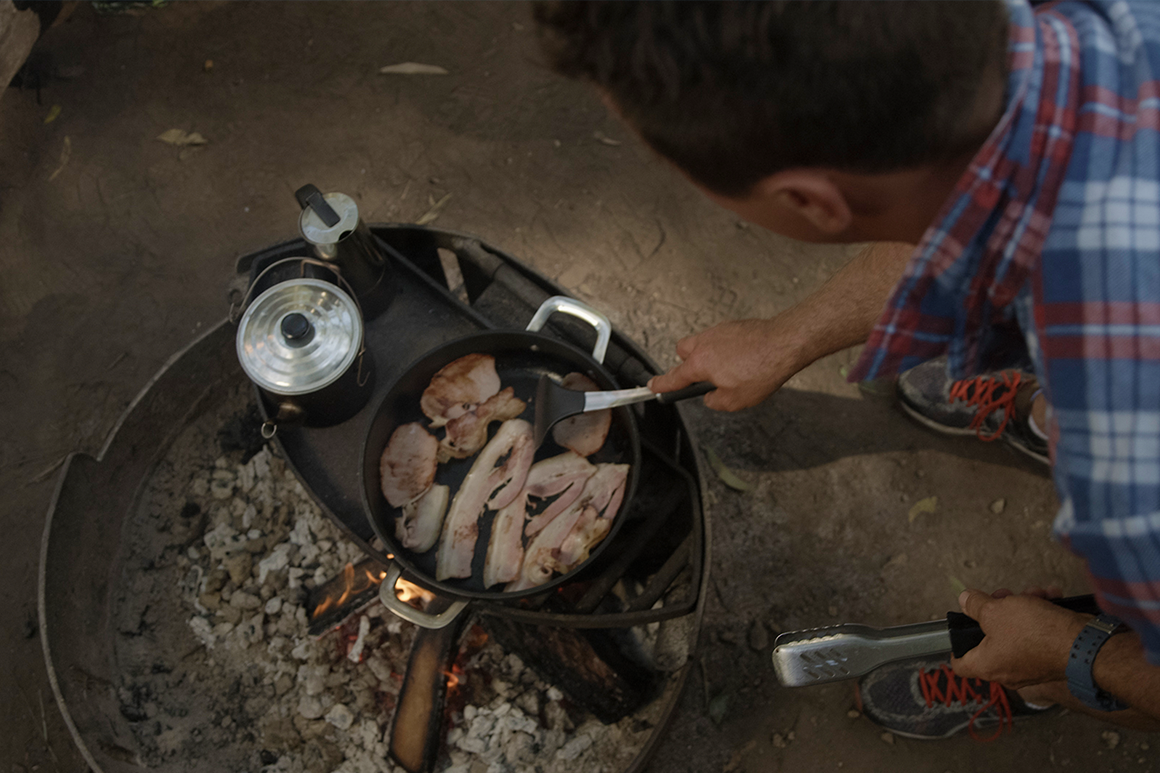 A man is cooking bacon and boiling a teapot over a campfire.