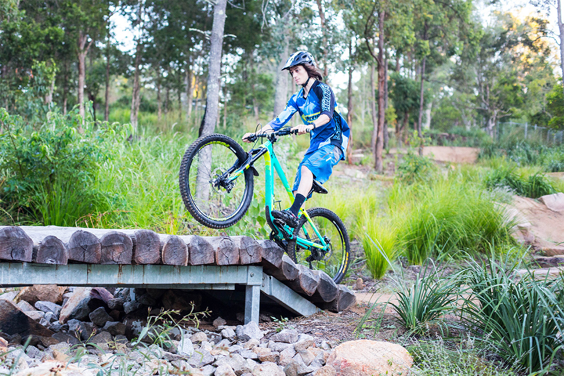 A boy in blue riding gear rides his mountain bike up a log ramp on a technical trail against a backdrop of green forest.