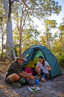 Photo of two walkers sitting around a camp stove at their tent.