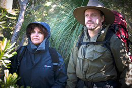 Photo of two walkers in wet weather gear and hats.