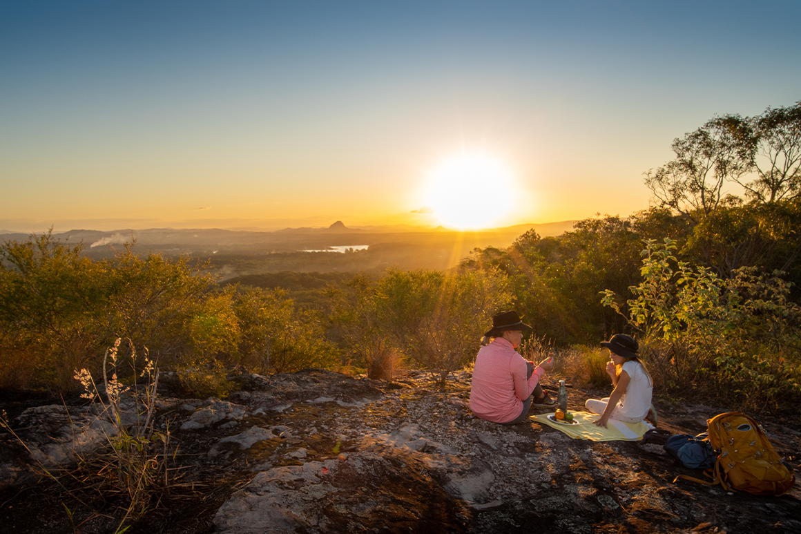 Hikers snack on a rock while enjoying view.