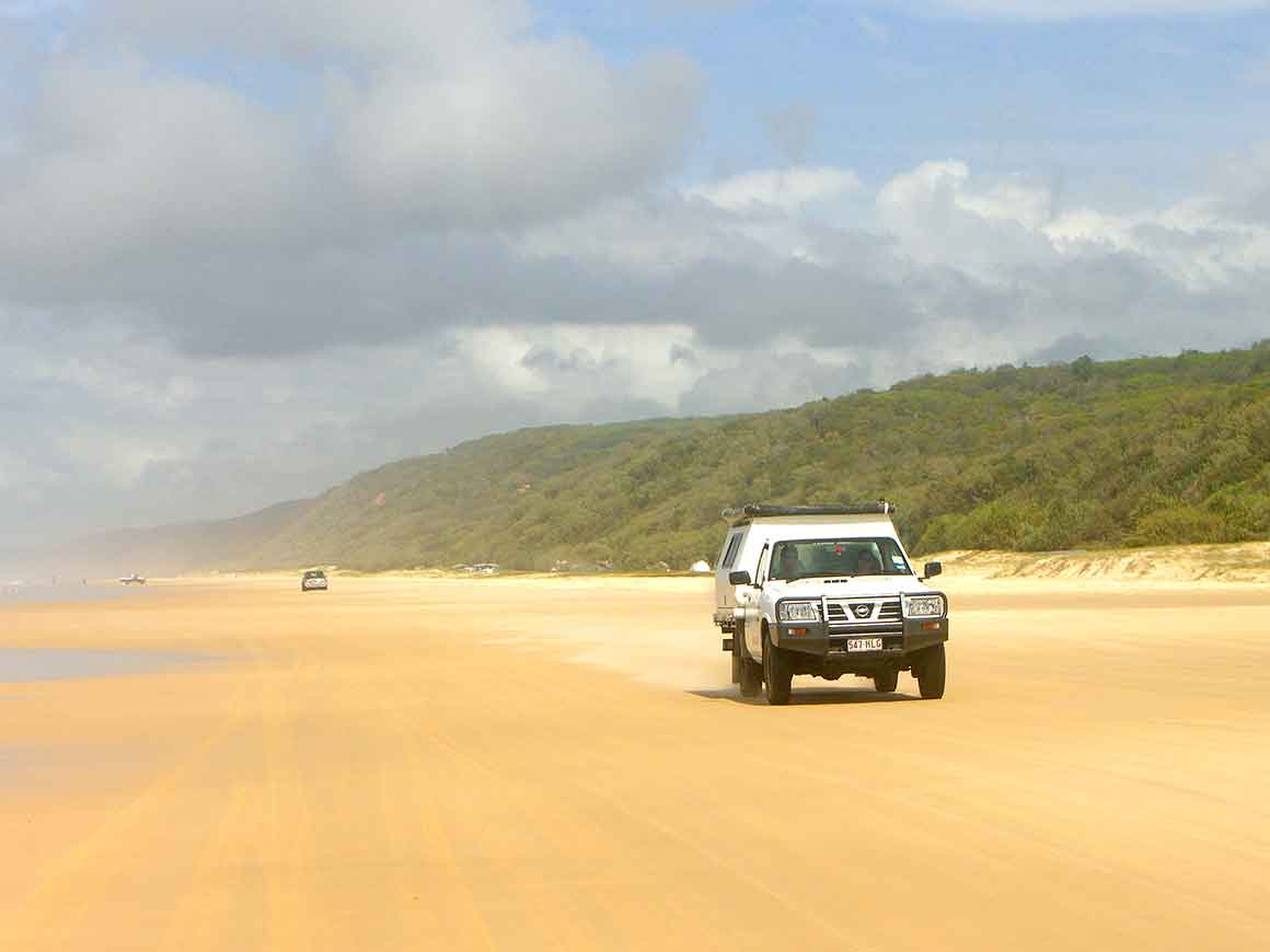 Four-wheel drive vehicle driving along golden sandy beach with high forested dunes on one side and blue ocean on the other, under big blue skies, with several cars coming behind in the distance.