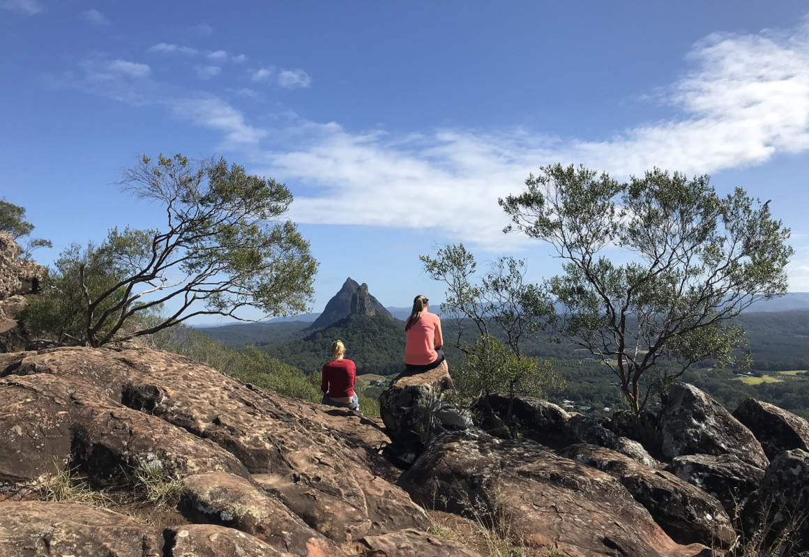 Two walkers in bright clothes sit on the rocky summit facing the distant views over two other peaks of the Glass House Mountains.