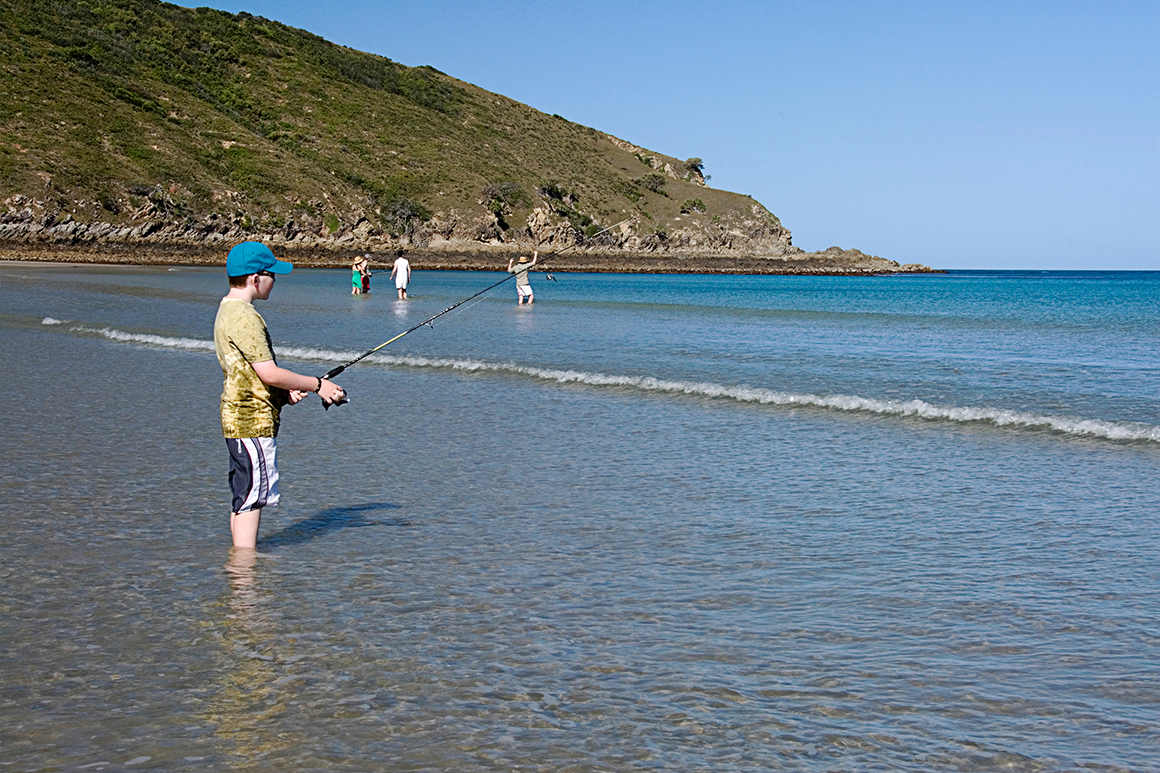 People with fishing lines stand in shallows on the beach with vegetated headland in background.