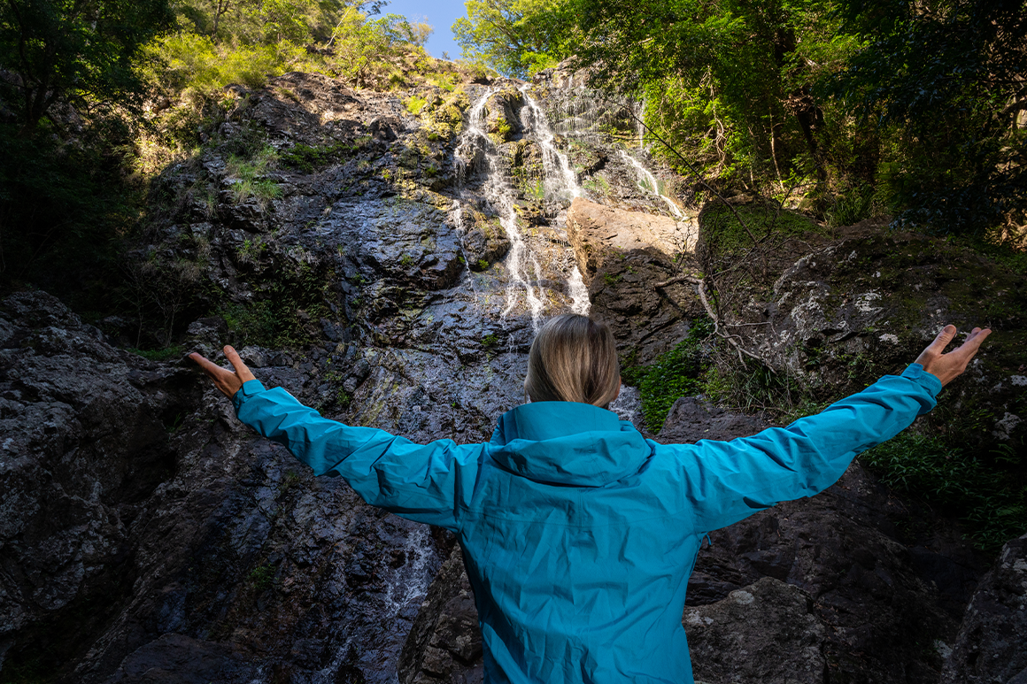 A hiker wearing a rain jacket is standing in front of a waterfall with her arms spread wide.